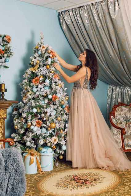 woman arranging white christmas tree